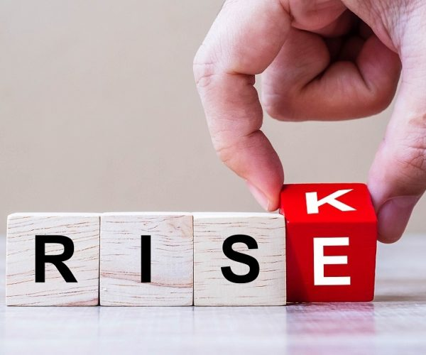 Businessman hand flipping wooden cube blocks with RISK change to RISE text on table background. strategy, analysis, marketing, management, opportunity and Crisis concepts